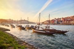Typical portuguese wooden boats, called  `barcos rabelos `transporting wine barrels on the river Douro with view on Villa Nova de. Gaia  in Porto , Portugal stock photos