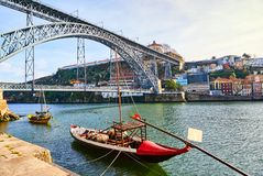 Typical portuguese wooden boats, called `barcos rabelos ` transporting wine barrels on the river Douro with view on Villa Nova de. Typical portuguese wooden royalty free stock photo
