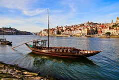 Typical portuguese wooden boats, called  `barcos rabelos `transporting wine barrels on the river Douro with view on Villa Nova de. Typical portuguese wooden stock image