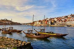 Typical portuguese wooden boats, called  `barcos rabelos `transporting wine barrels on the river Douro with view on Villa Nova de. Typical portuguese wooden royalty free stock photography