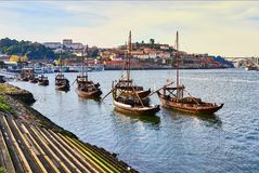 Typical portuguese wooden boats, called  `barcos rabelos `transporting wine barrels on the river Douro with view on Villa Nova de. Typical portuguese wooden stock images