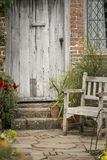 Typical quintessential old English country garden image of wooden chair next to vintage back door stock photography