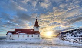 Typical red colored wooden church in Vik town, Iceland in winter. Sunrise light stock image