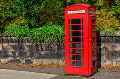 Typical red English telephone booth in the park. Typical British telephone booth in the park Stock Photography