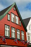 Red house with norwegian flags in Bergen. Typical red norwegian houses with norwegian flag in Bergen in Norway royalty free stock photos