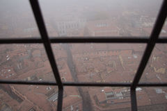 Typical red roofs of Bologna in a foggy day. View from a narrow window of Asinelli Tower. Emilia Romagna , Italy. royalty free stock image