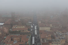 Typical red roofs of Bologna and a market in a foggy day. View from Asinelli Tower. Emilia Romagna , Italy. Stock Photos