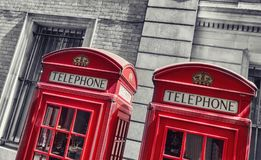 Typical red telephone booths in London. Traditional red phone booths closeup at london in black and white colors. ideal for websites and magazines layouts Stock Photo