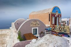Typical restaurant in the Oia village on a rare rainy day, Santorini, Greece stock images