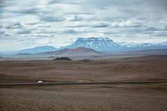 Typical ring road view with empty road and snowy mountains and one lonely car. In Iceland in summer stock image