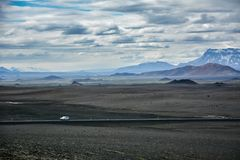 Typical ring road view with empty road and snowy mountains and one lonely car in Iceland. In summer royalty free stock photography