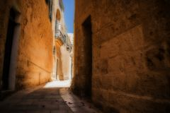 Typical Road in the Silent City. A typical narrow and historical road inlcuding cobblestone walls in Mdina, Malta Royalty Free Stock Photo