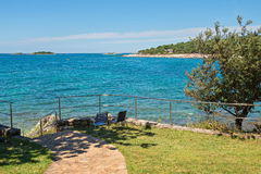 Typical rocky beach with two chairs in Istria Royalty Free Stock Photos