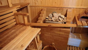 A typical Russian bathhouse. A steam room in a Russian bath. The room is decorated with wood. There is a tub of water and a stove with hot stones, which make stock video footage
