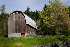 Typical Rustic Old Round Roofed Barn. A typical rustic old round roofed barn with typical common vertical lap board siding barn details under clear blue skies Royalty Free Stock Photos