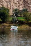 Typical sailing boat of the Nile River in Egypt called Felucca stranded on the river bank, in a green area but with a desert sands. Tone wall behind Stock Image