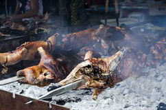 Typical Sardinian food. Piglets roast cooking in the bbq in a ty Royalty Free Stock Images