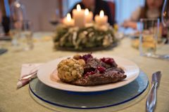 Festive Christmas dinner in Austria. Typical seasonal venison filet dish medium rare, decorated with red cabbage and chestnut, bread dumpling and cranberry sauce Stock Images
