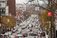 Typical Shopping street in Cote des Neiges district, with small and medium businesses, cars passing by in a traffic jam. MONTREAL, CANADA - NOVEMBER 7, 2018 stock photos