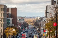 Typical Shopping street in Cote des Neiges district, with small and medium businesses, cars passing by in a traffic jam. MONTREAL, CANADA - NOVEMBER 8, 2018 stock image