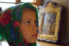 Beautiful little girl in scarf in church. Orphan stock images
