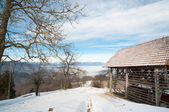 Typical Slovenian shed in mountains. Rural Alpine view of typical Slovenian shed on mountains background under blue sky near hiking trail in snow Stock Image
