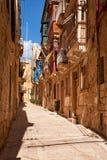 A typical small street (Saint Dominic) of Birgu, Malta. A view of the typical small street (Saint Dominic) with traditional maltese balconies on Birgu, Malta Stock Photo
