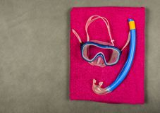 Snorkel, diving mask and towel. Typical snorkeling equipment - snorkel, diving mask on the towel Royalty Free Stock Photo