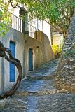 Typical Spanish Alleyway. A gnarly tree frames a cobbled stone road with homes in Spain Royalty Free Stock Photo