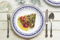 Typical Spanish and Andalusian Cod with Samfaina served on a rustic wooden table next to somw white wine and floral decoration. Top view and empty copy space stock photography