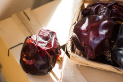 Typical Spanish nyora peppers dried in the sun, on thread in wicker basket on wood box Stock Photos