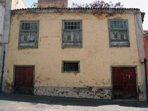 Typical Spanish old house in tenerife with yellow plaster walls. And weeds growing from the roof fading green windows on a sloping street Royalty Free Stock Photos