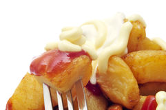 Typical spanish patatas bravas, fried potatoes with a hot sauce. Closeup of some typical spanish patatas bravas, fried potatoes with a hot sauce, on a white stock images
