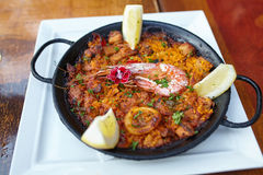 Typical spanish seafood paella dish. With prawn and lemon in traditional pan in restaurant royalty free stock photo