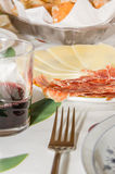Typical spanish tapa with slices of serrano ham and manchego che Stock Image