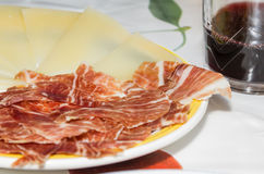Typical spanish tapa with slices of serrano ham and manchego che Stock Images