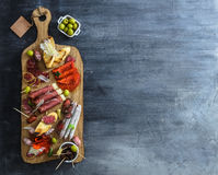 Typical spanish tapas concept. include variety slices jamon, chorizo, salami, bowls with olives, peppers, anchovies Royalty Free Stock Images