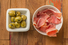 Typical Spanish tapas: serrano ham and green olives Royalty Free Stock Photos