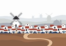 Typical Spanish village La Mancha with windmills in the background landscape. Road on the ground in the foreground.  Royalty Free Stock Photo