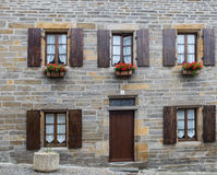 Typical stone construction with series of wooden windows with fl. Le Conquet, Bretagne, France - Ago 2, 2016: Typical stone construction with series of wooden Royalty Free Stock Image