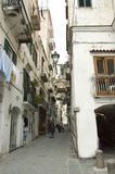 Typical street in Amalfi, Italy. Typical small European street on Mediterranean coast with stores, white houses and clotheslines, Amalfi, Italy royalty free stock photography