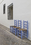 Typical street of an Andalusian village. Street of a typical Andalusian village, with three wooden chairs on the sidewalk Royalty Free Stock Photos