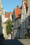 Typical Street In Brugges, Belgium. Typical street, buildings, red tile roofs and cobblestone street in Brugges, Belgium Royalty Free Stock Photo