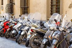 A typical street of Florence with motorcycle scooters parked in Royalty Free Stock Photos