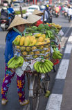 Typical street fruit vendor with palm-leaf conical hat moving at the street in road. Stock Images