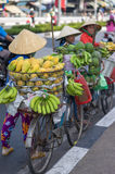 Typical street fruit vendor with palm-leaf conical hat moving at the street in road. Royalty Free Stock Photography