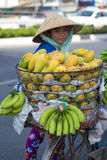 Typical street fruit vendor with palm-leaf conical hat moving at the street in road. Stock Photos
