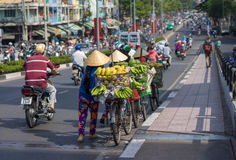 Typical street fruit vendor with palm-leaf conical hat moving at the street in road. Royalty Free Stock Photo