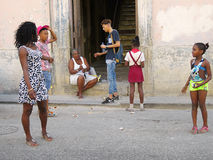 Typical street life in Havana, Cuba. Cuba, Havana - 07 April, 2016: a typical street life in Havana, with pedestrians walking in different directions, a mother Royalty Free Stock Photo