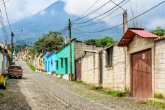 Typical street scene looking up to Agua volcano in Guatemalan vi. San Juan del Obispo, Guatemala - June 24, 2017: Typical street scene of houses & stores looking royalty free stock photo